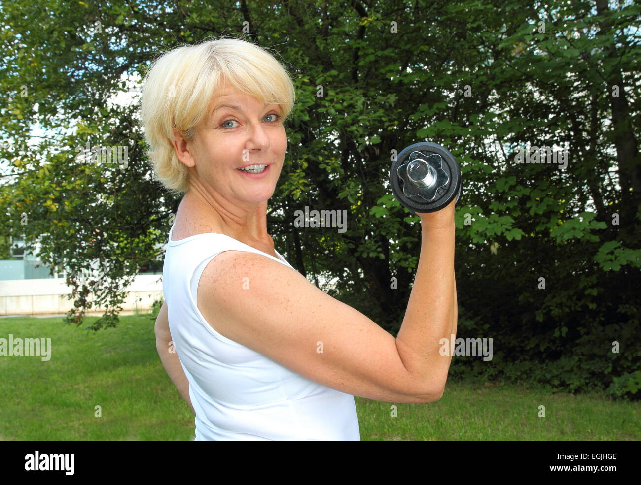 A Elderly woman doing outdoor training in a park with dumbbell - Stock Image
