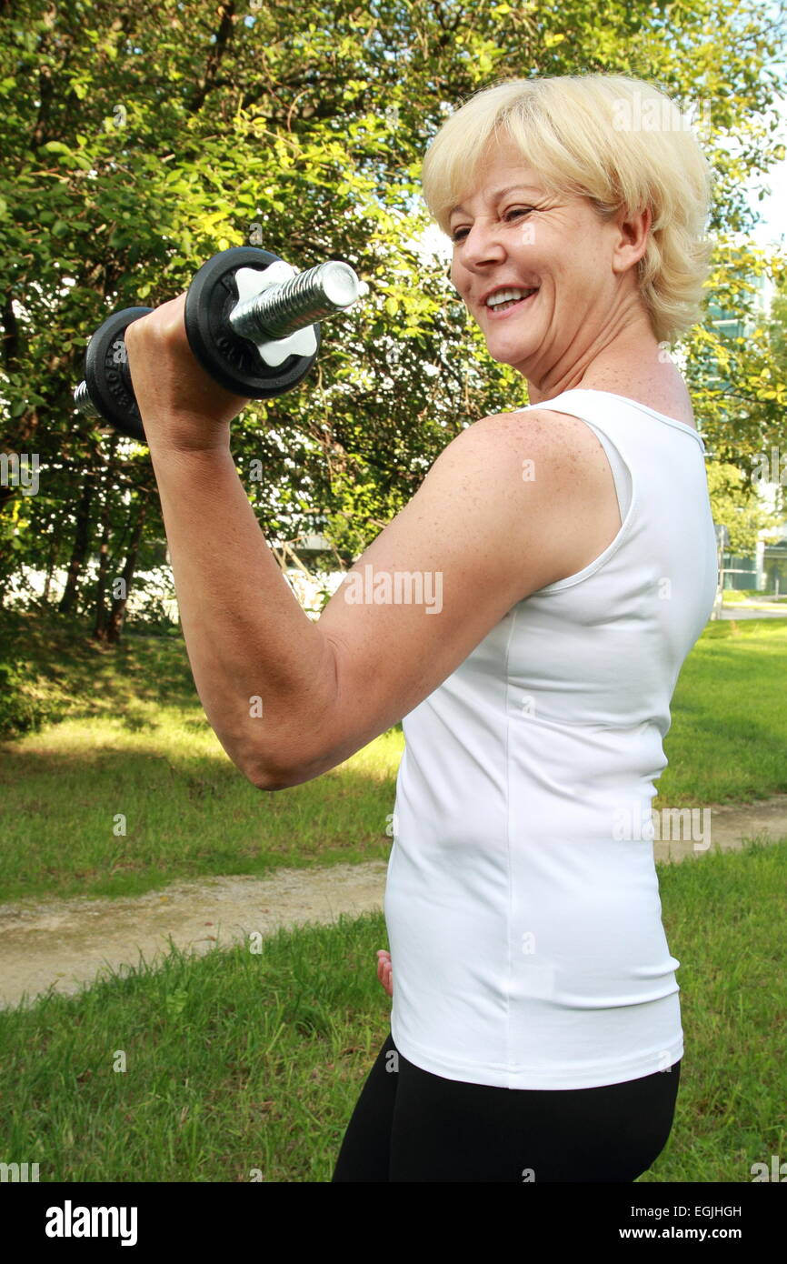 A Elderly woman outdoor training with dumbbell - Stock Image