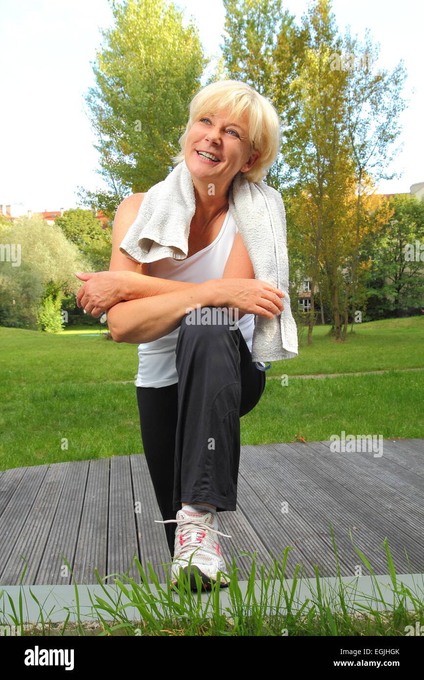 A Senior woman doing sport with towel over neck - Stock Image
