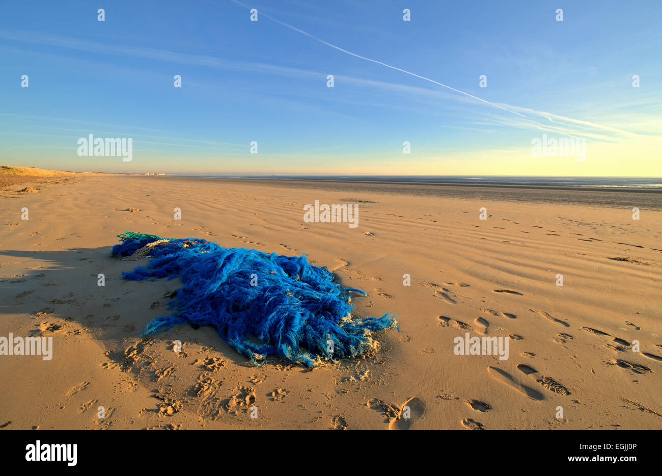wide angle shot of a blue discarded fishing net on beach - Stock Image