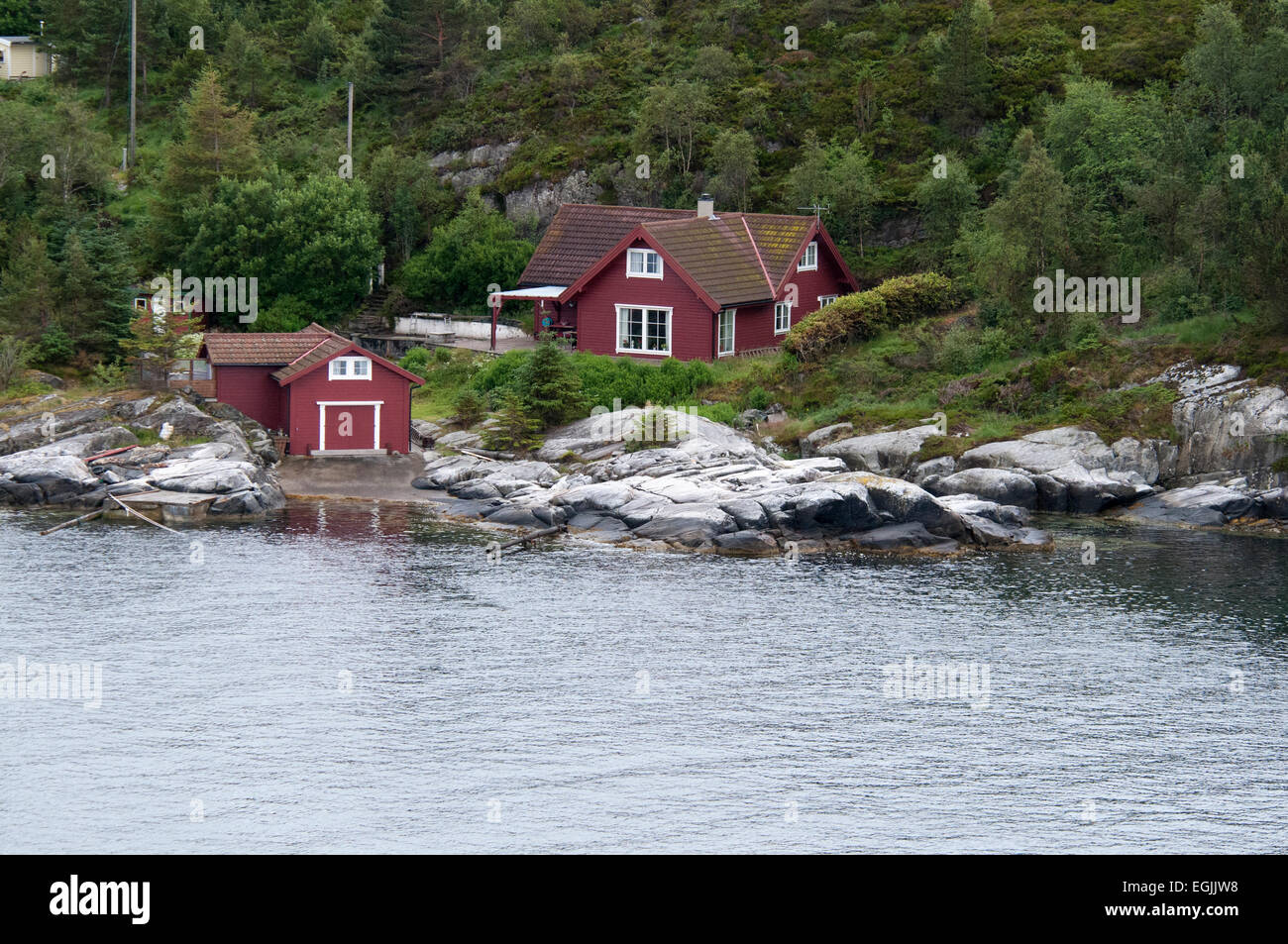 In the fjords just out of the Norwegian city of Bergen some holiday houses are situated just at the shoreline.  - Stock Image