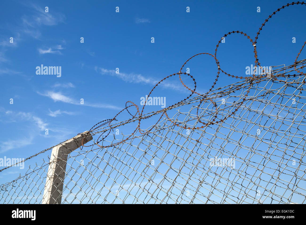 Metal fence with barbed wire over blue sky background - Stock Image