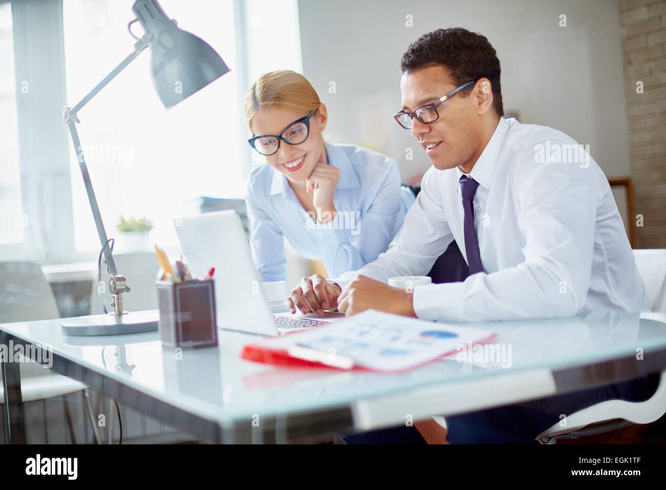 Charming secretary and her boss browsing data for new project at meeting - Stock Image