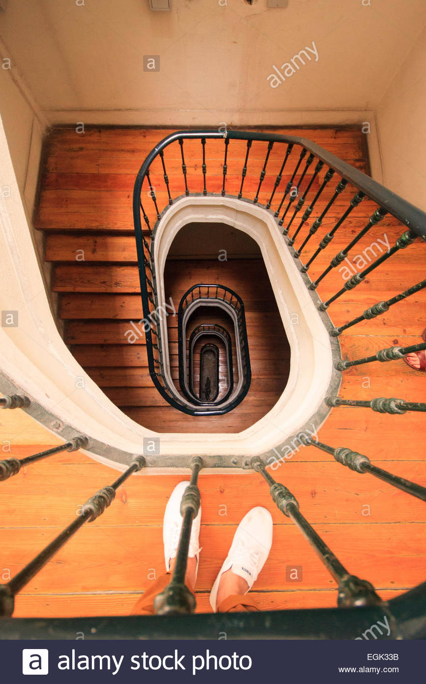 Overhead view of spiral staircase and human feet in white shoes - Stock Image