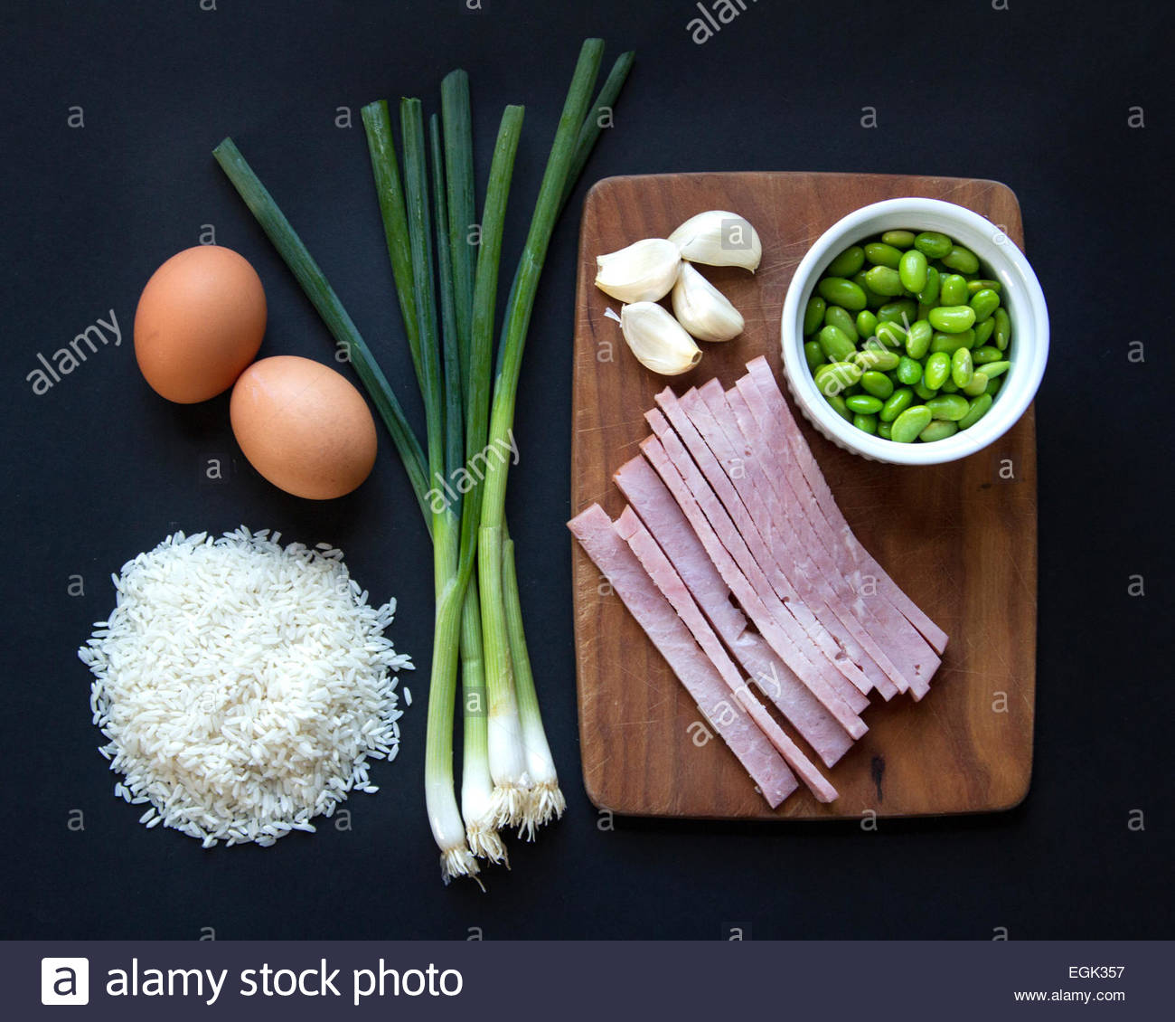 Overhead view of food ingredients on black background - Stock Image