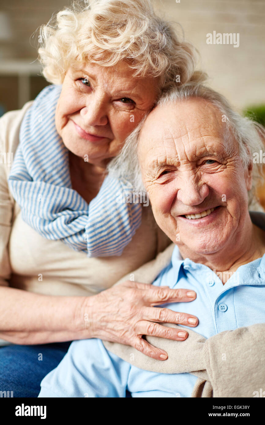 Affectionate seniors looking at camera with smiles - Stock Image