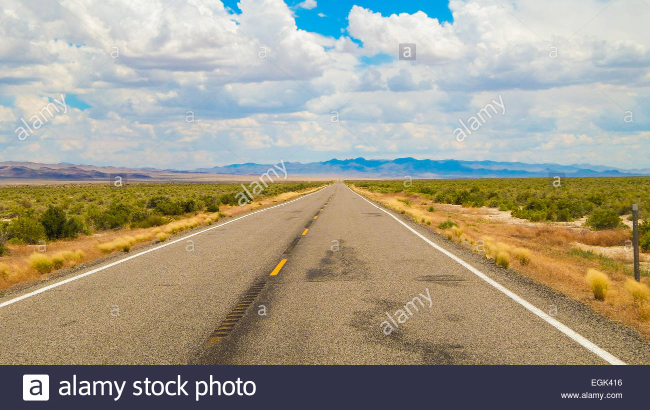 View of empty road with mountains in distant - Stock Image
