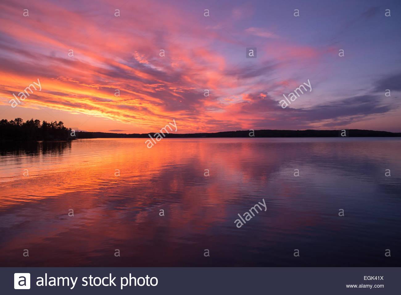 Idyllic sunset over lake - Stock Image