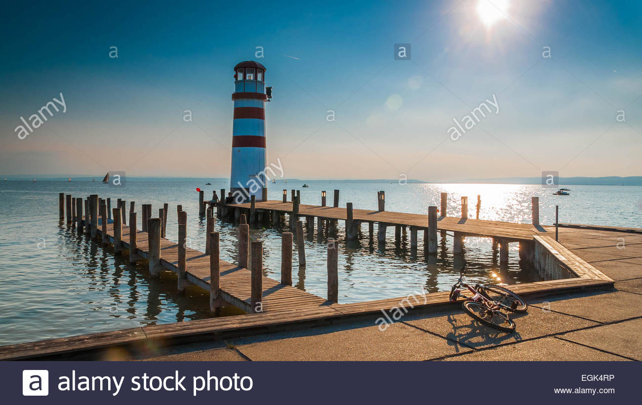 Pier with lighthouse in sunlight - Stock Image