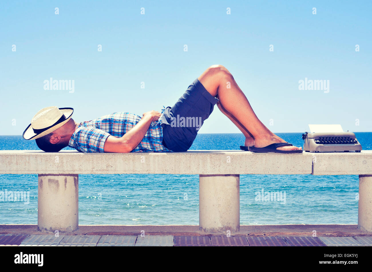 an old typewriter with a blank page and a young man lying down in a street bench near the sea, while is waiting - Stock Image
