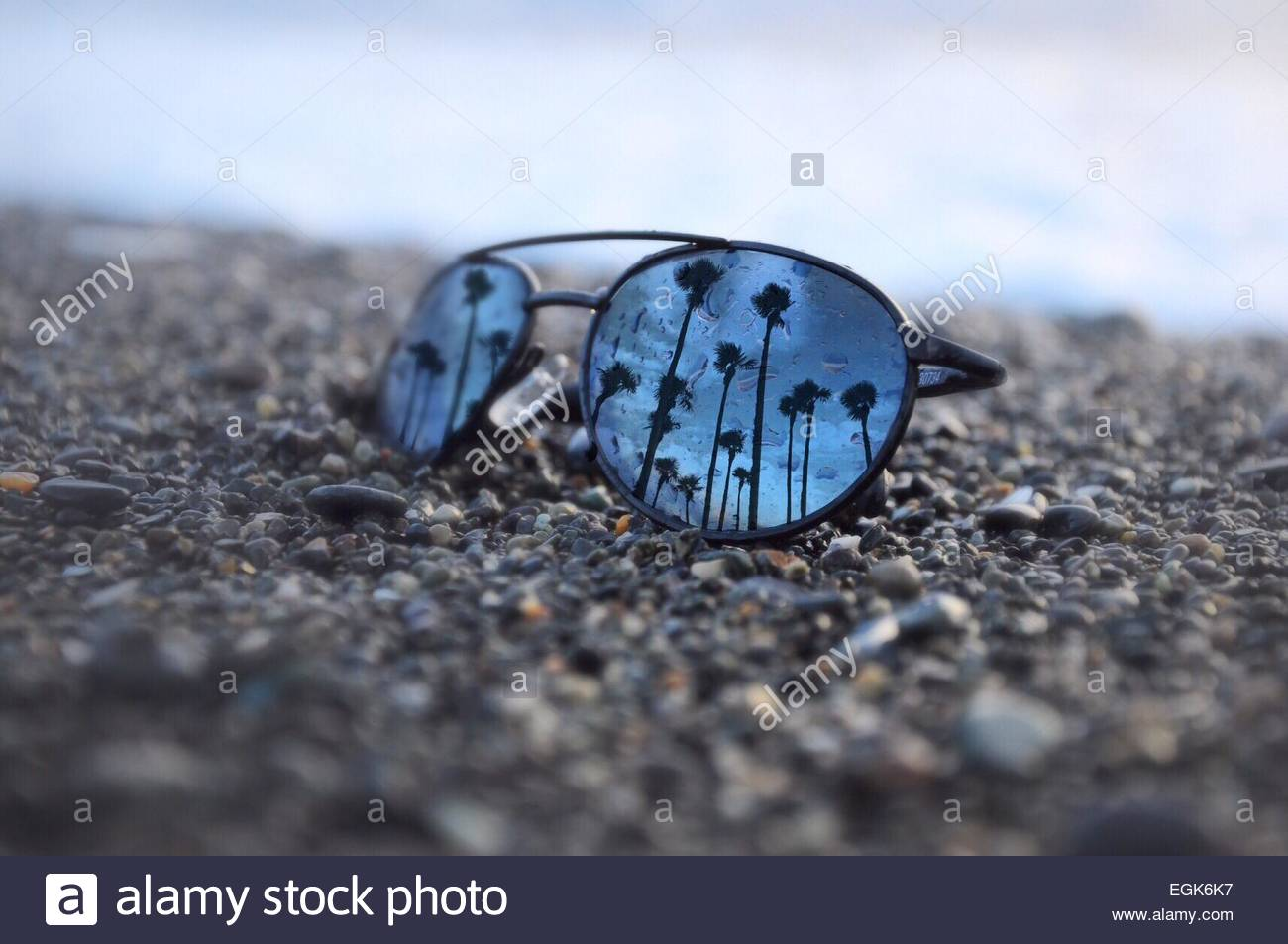 07dbe603a1 Mirrored sunglasses on pebbled beach with reflection of palm trees against  sky