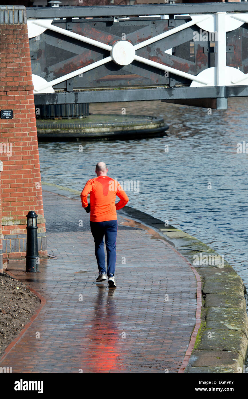 Man running on canal towpath, Birmingham city centre, UK - Stock Image