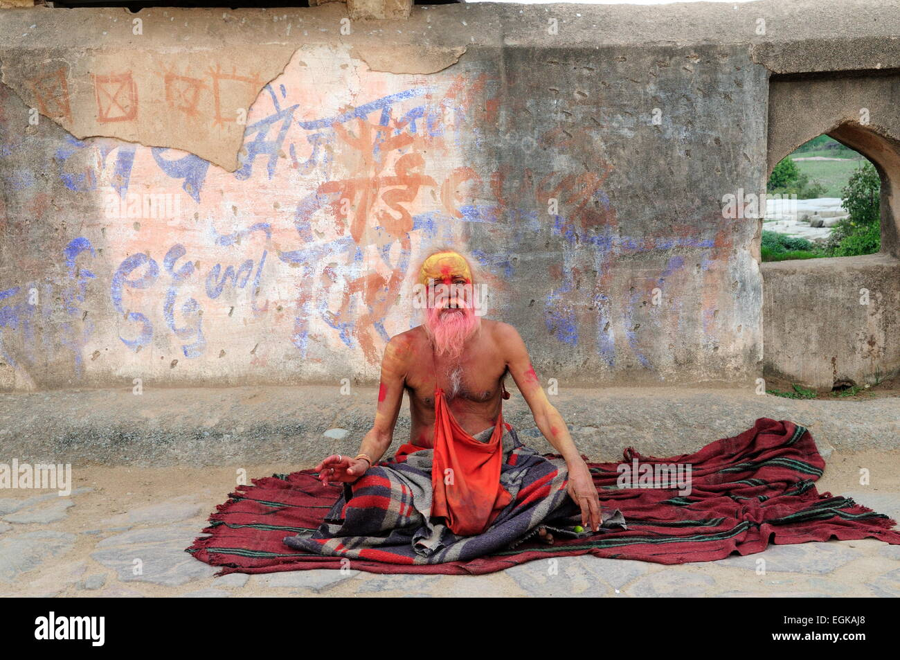 Indian Holy Man Sadhu sitting on a bridge over the Betwa River Orchha  Madhya Pradesh India - Stock Image