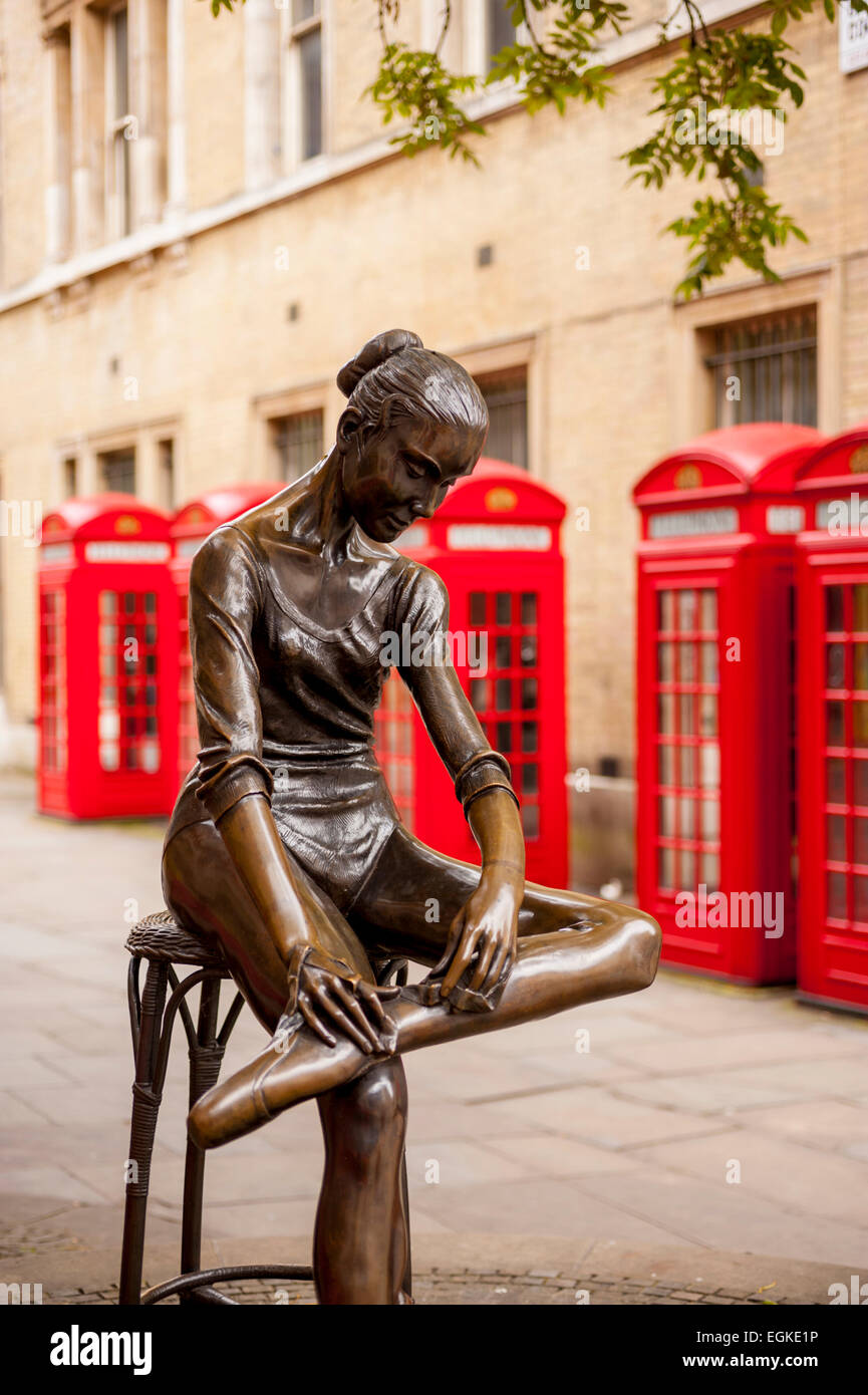 Row of red phoneboxes in Broad court, Drury lane London with statue of dancer in foreground - Stock Image
