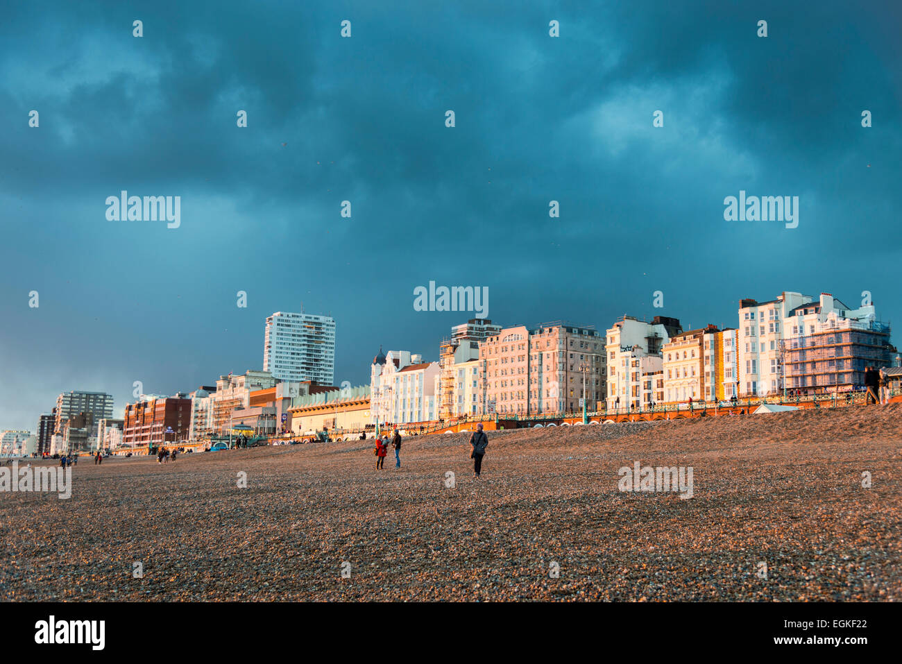 Sun lighting the beach, hotels and buildings on the seafront at Brighton on a stormy evening and a black cloudy - Stock Image