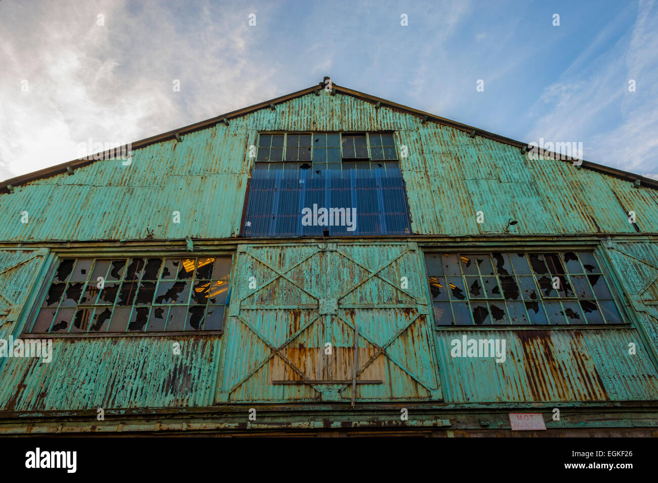 gable of empty warehouse near the canal basin at gravesend kent. green paint and rust covering the coregated sheet - Stock Image