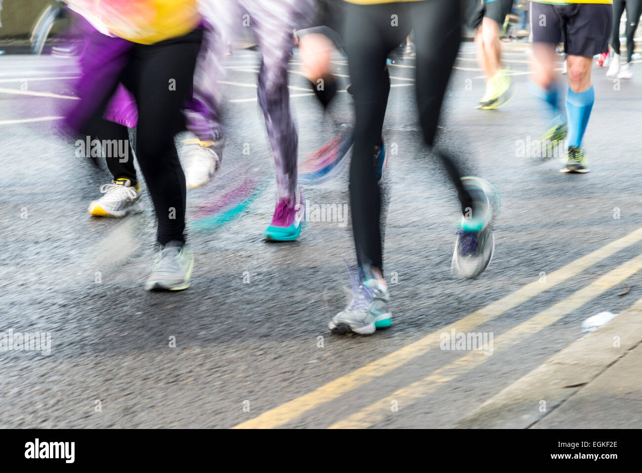 Blurred legs and feet of marathon runners.  Motion blur athletes running. - Stock Image