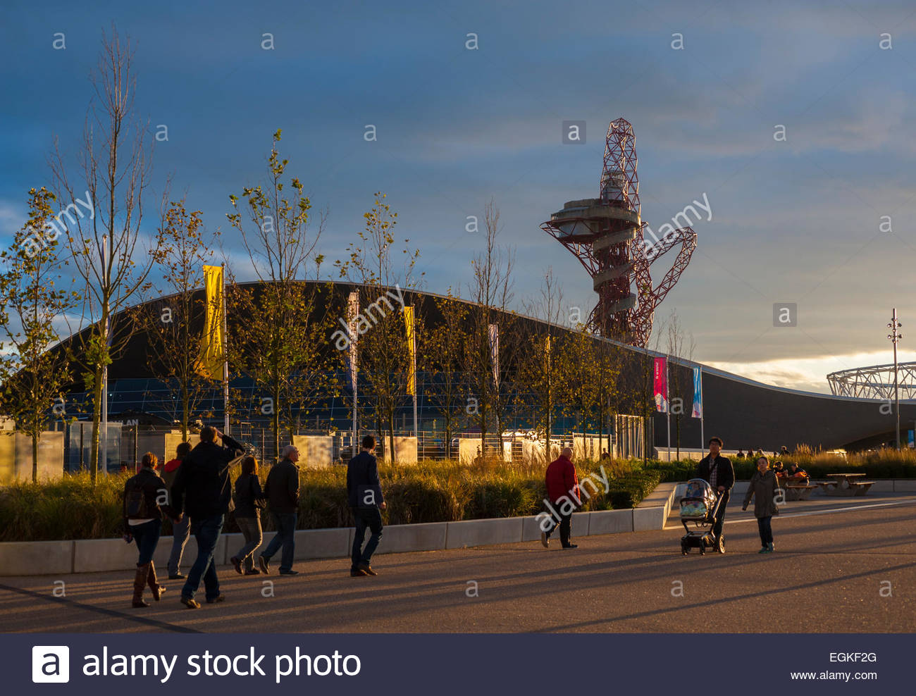 people leaving the queen elizabeth olympic park strartford. with evening light hitting the orbital tower and the - Stock Image