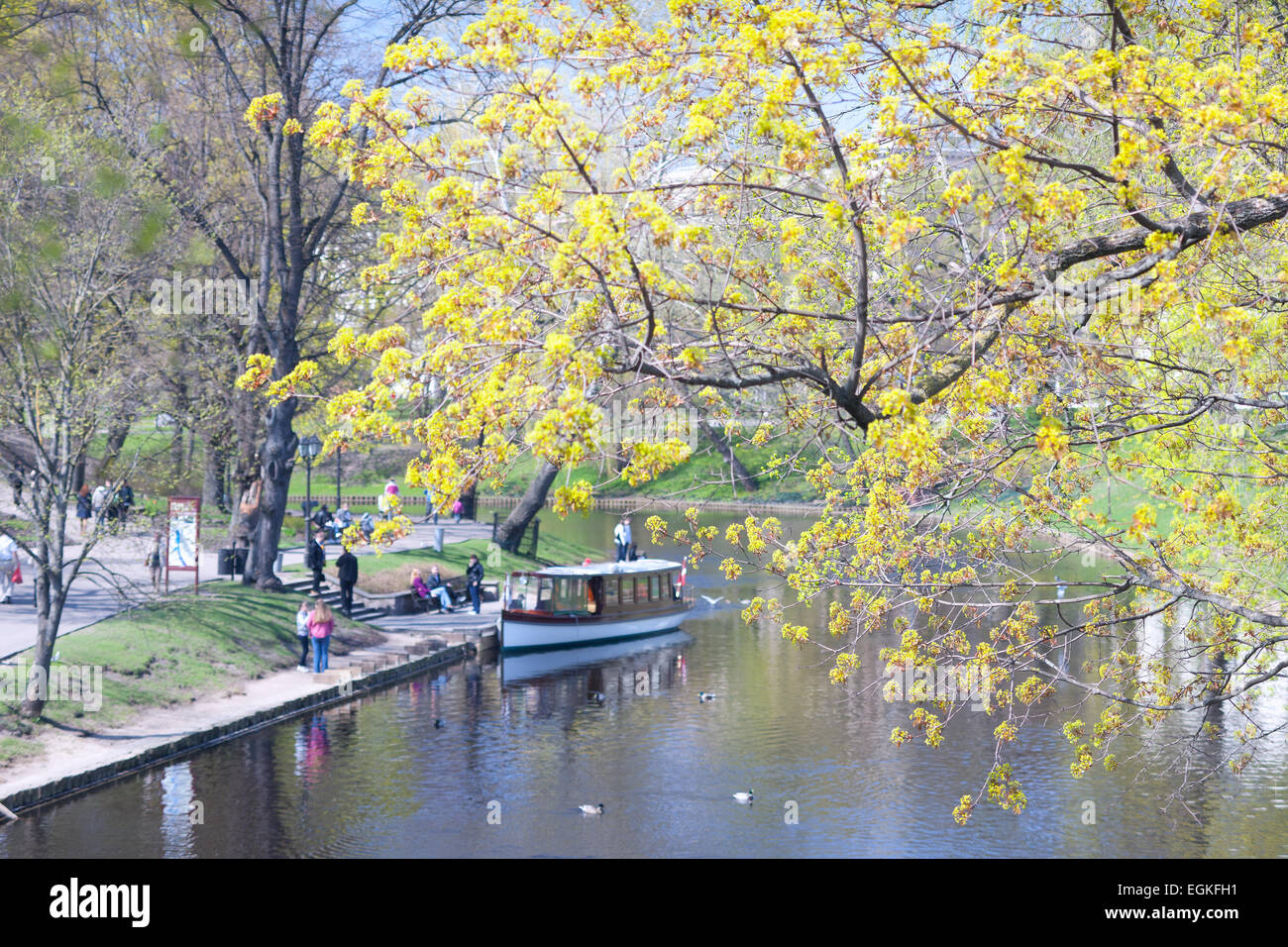 People walk in the park in pleasure boats on the city channel in Riga in spring - Stock Image