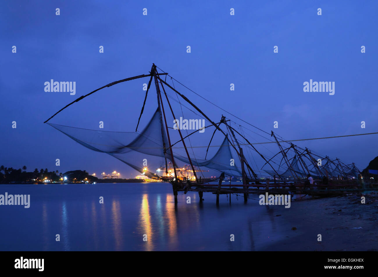 Chinese Fishing nets at Fort Kochi, Kerala, South India at evening blue hour with Vallarpadom Container Terminal - Stock Image