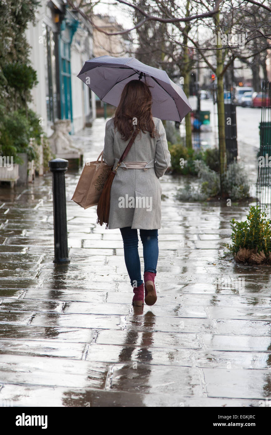 Behind view of lady holding umbrella walking in the rain down street in Notting Hill, London. - Stock Image