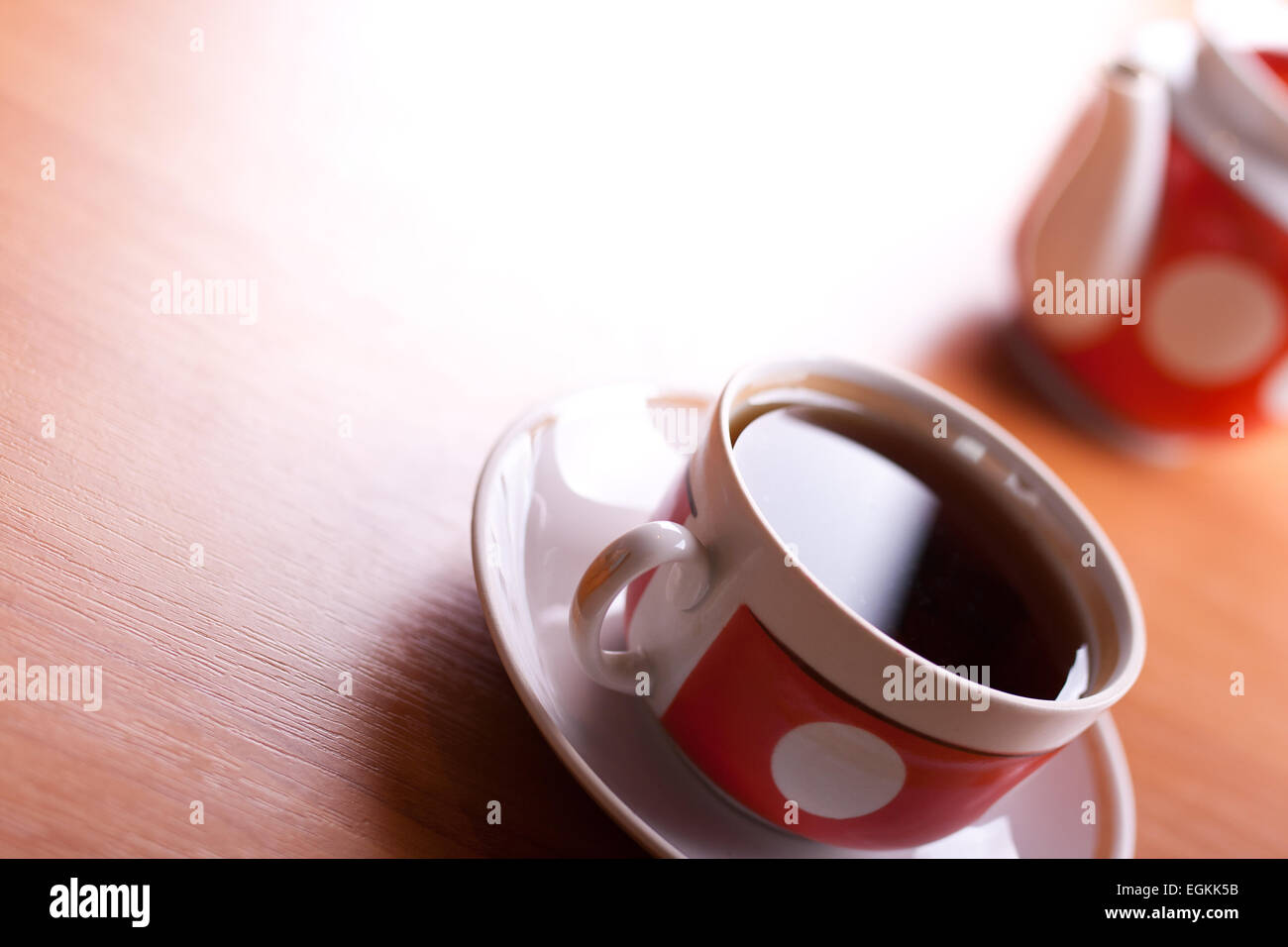 cup of black tea close up on a table with teapot blurred on background - Stock Image