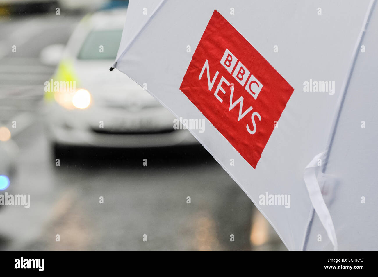 Ballyclare, Northern Ireland. 11th September 2013 -  Journalist holds a BBC News umbrella while watching police - Stock Image