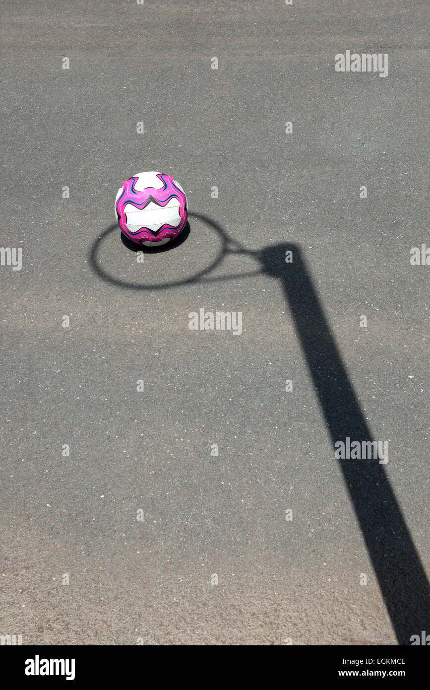 Netball resting on the ground, with the shadow of the hoop surrounding the ball. - Stock Image