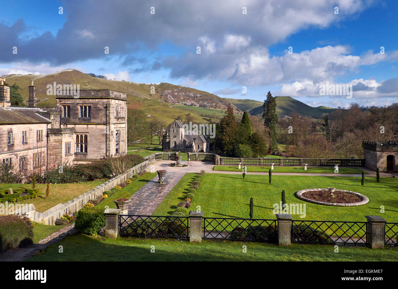 Ilam Hall Youth Hostel and Church of the Holy Cross in Ilam Park with Bunster Hill and Thorpe Cloud in distance. - Stock Image
