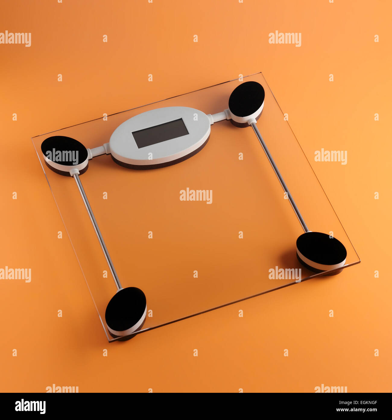Bathroom digital scales from transparent glass on an orange background. - Stock Image