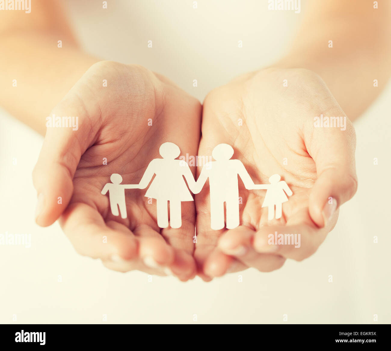 womans hands with paper man family - Stock Image