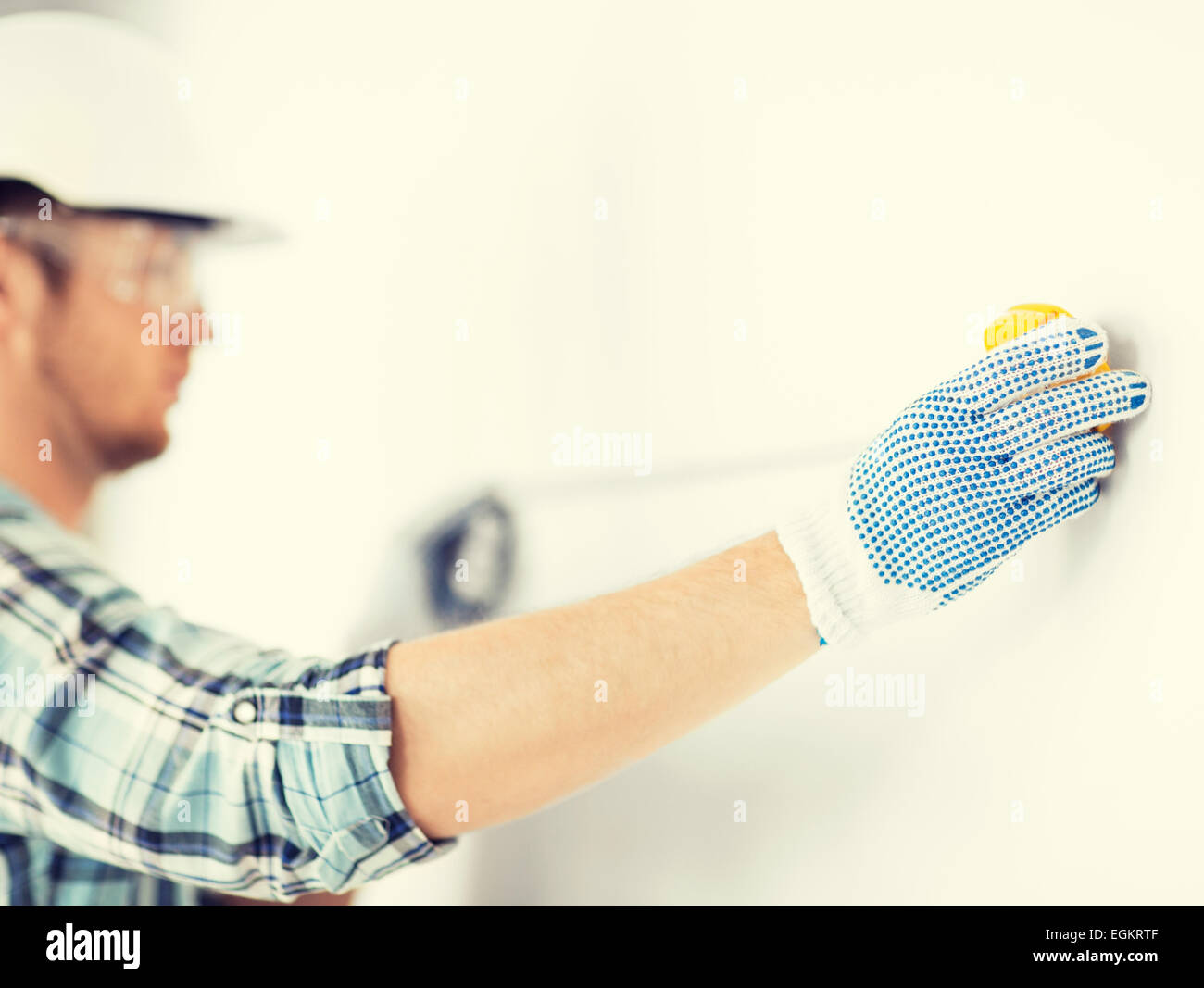 architect measuring wall with flexible ruler - Stock Image