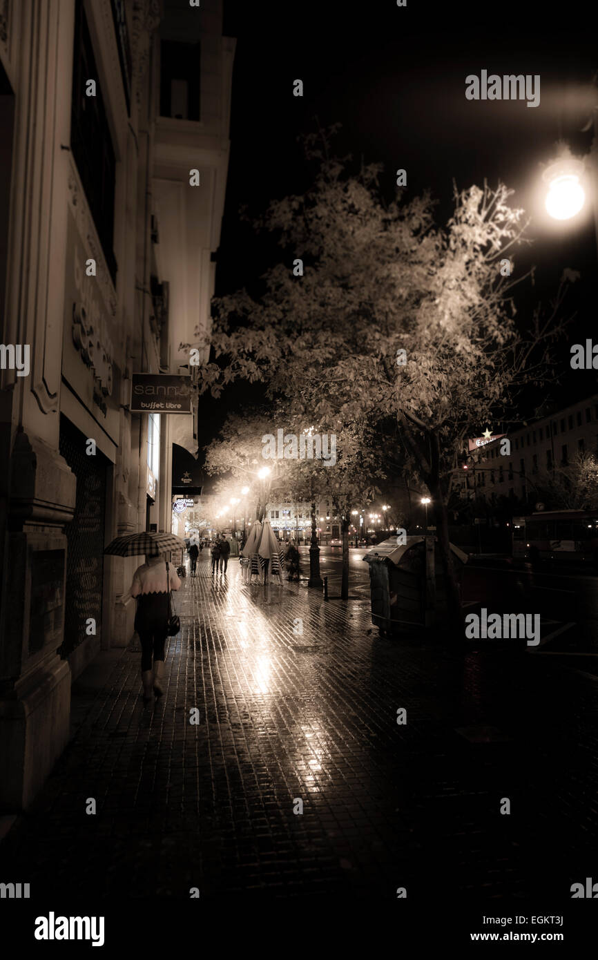 Wet and rainy city streets of Valencia at night with street lights and reflections - Stock Image