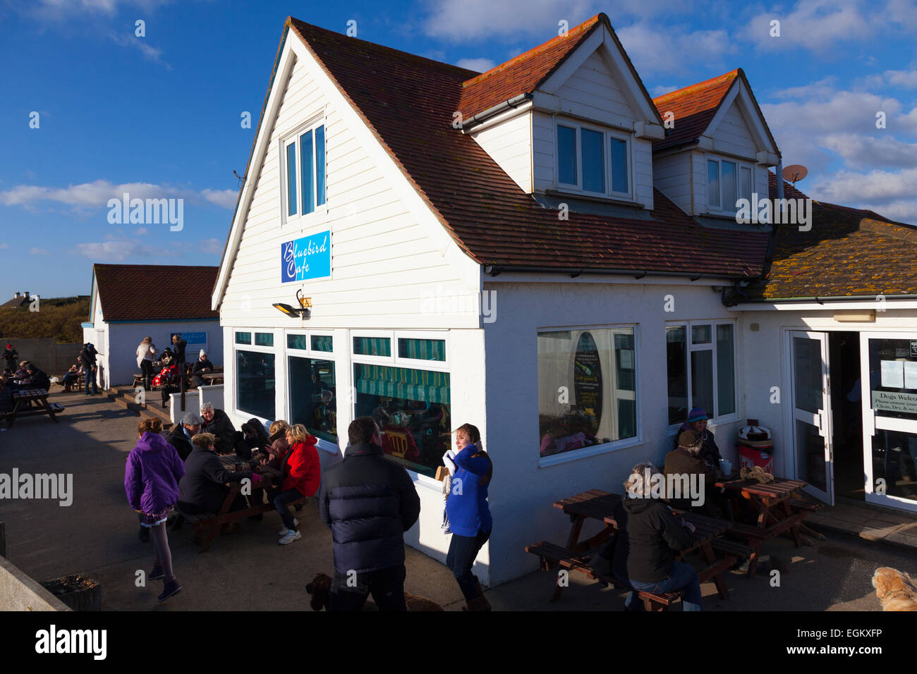Customers sitting outside the Bluebird beach cafe on Ferring beach in the winter sunshine Stock Photo