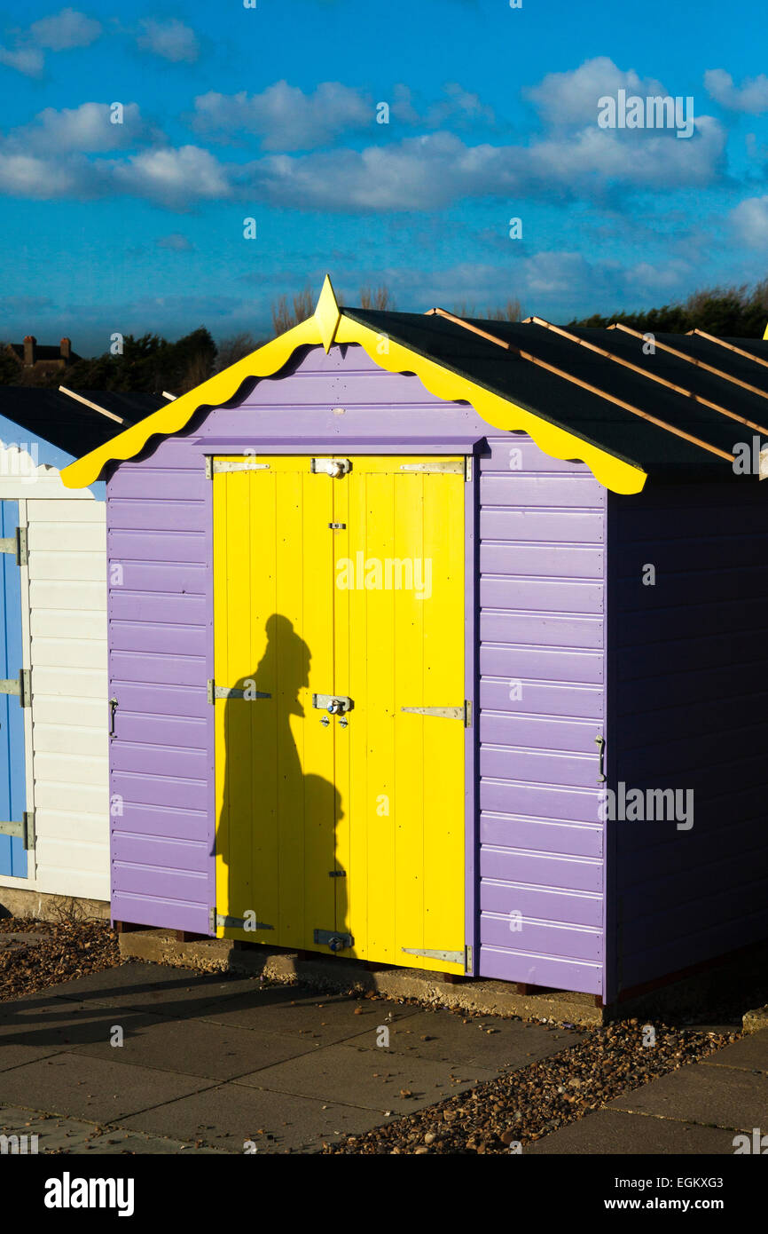 Shadow of people cast on colourful beach hut by low winter sun Stock Photo