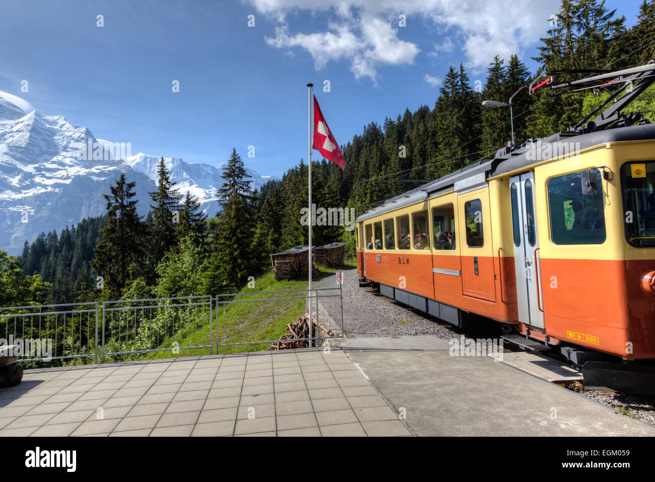 Train leaving station at Grutschalpin in the Jungfrau Region of the Bernese Oberland of Switzerland headed to Murren. - Stock Image