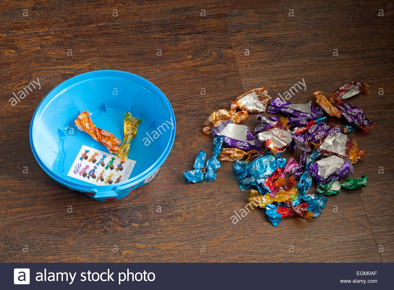 An empty tub of roses chocolates and discarded wrappers - Stock Image