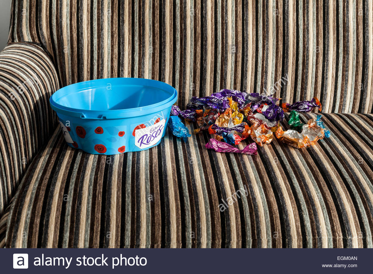 An empty tub of chocolates and discarded wrappers - Stock Image
