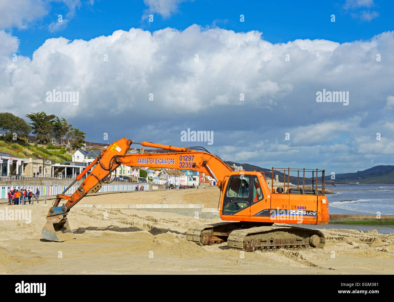 Levelling the beach at Lyme Regis with  a JCB digger, Dorset, England UK - Stock Image