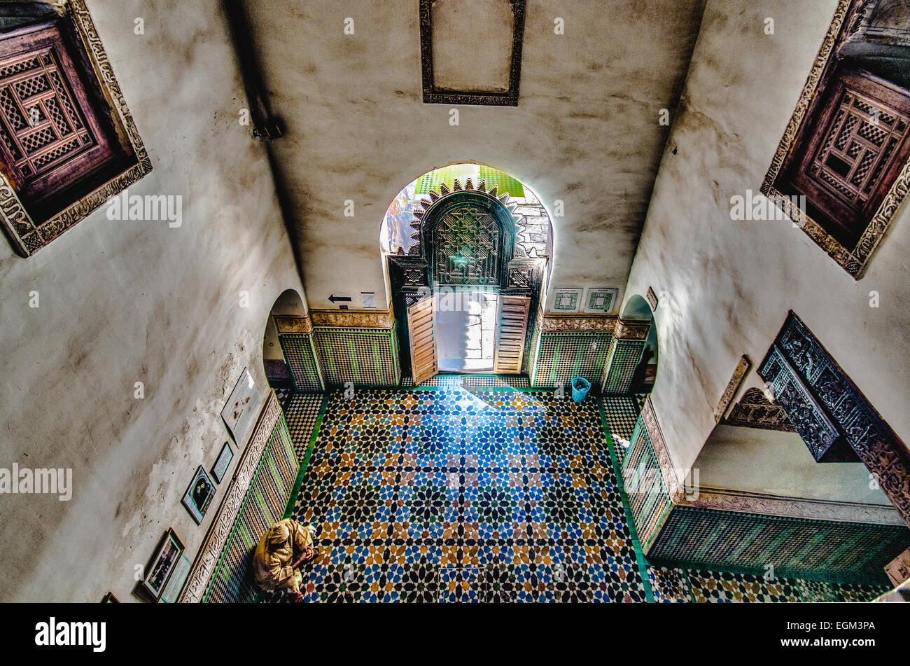 A man sits on a mosaic tiled floor in the Museum of Marrakech - Stock Image