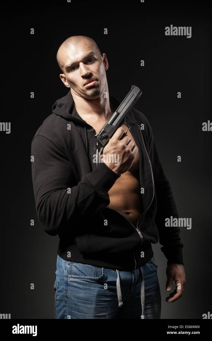 male gangster holding a gun isolated on dark background - Stock Image