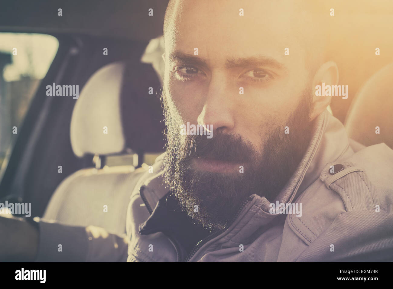 Young handsome man driving his car on a beautiful sunny day. Retro tones. - Stock Image