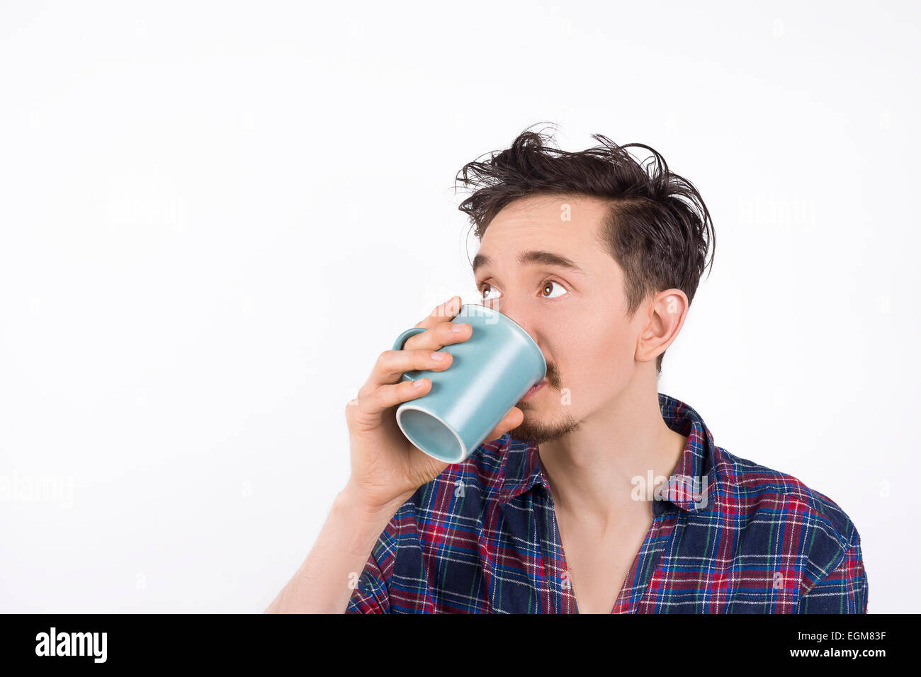 Portrait of a man wearing pajamas drinking coffee or tea and looking to his right. Isolated on white - Stock Image