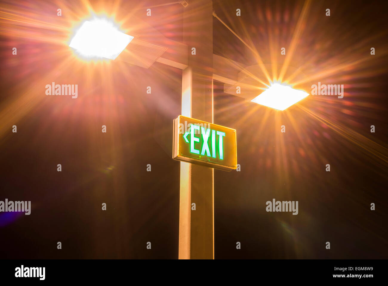 Bright lights above a lighted exit sign at night. - Stock Image