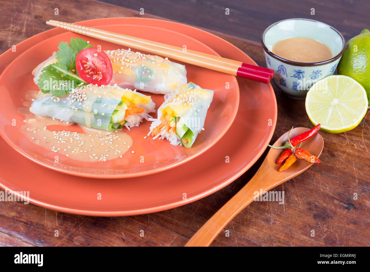 close up of vegan rice paper rolls with tahini dressing and sesame seeds - Stock Image