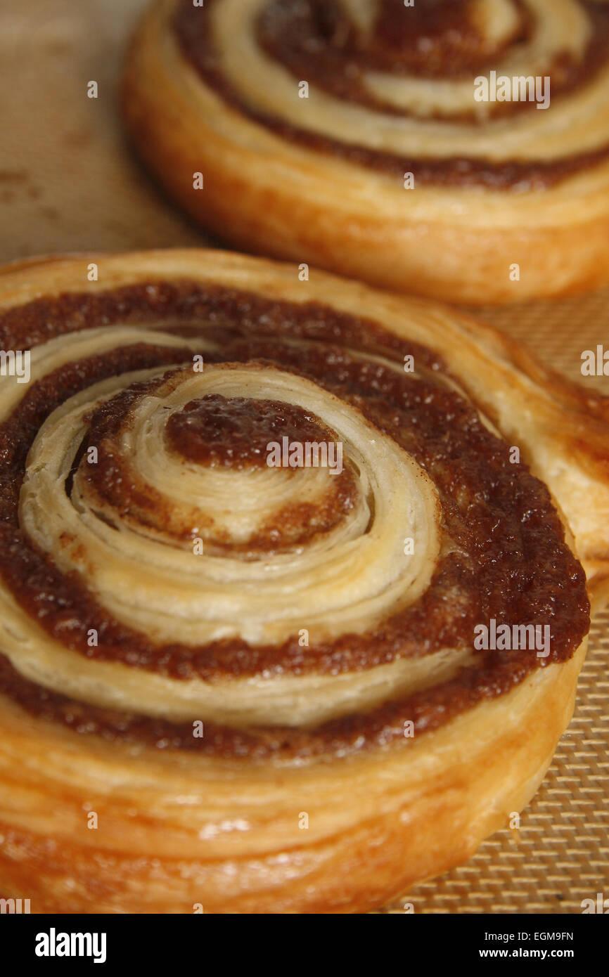 cinnamon swirls on baking mat fresh from the oven - Stock Image