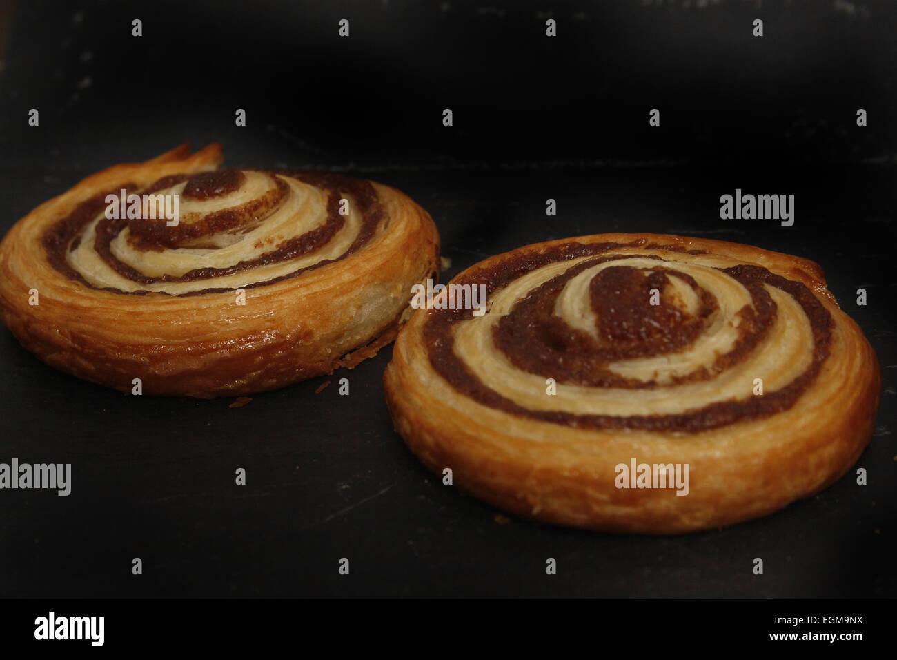 freshly baked cinnamon swirls on a black slate - Stock Image