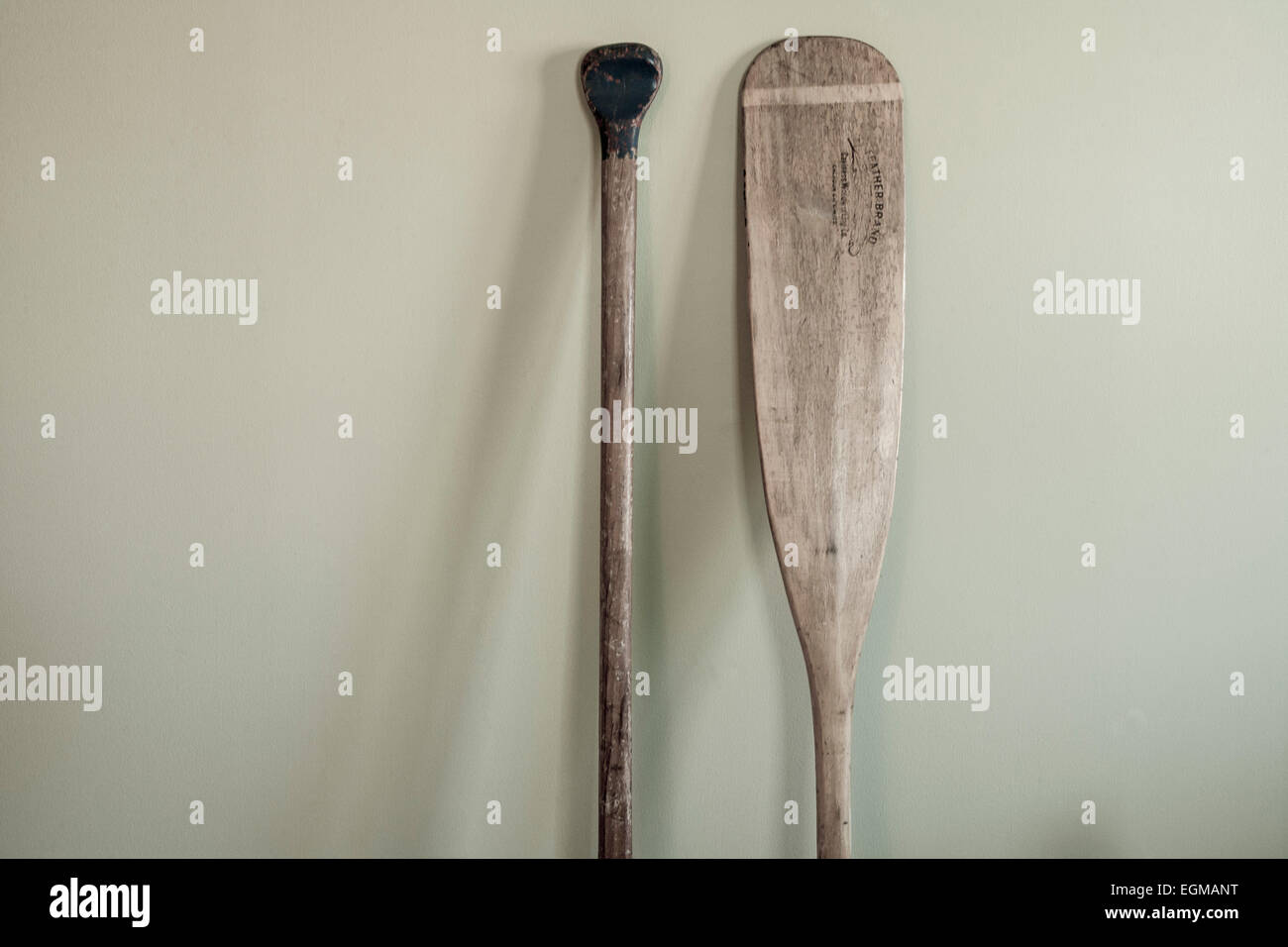 Decorative Canoe Paddles Leaning Against Bedroom Wall - Stock Image