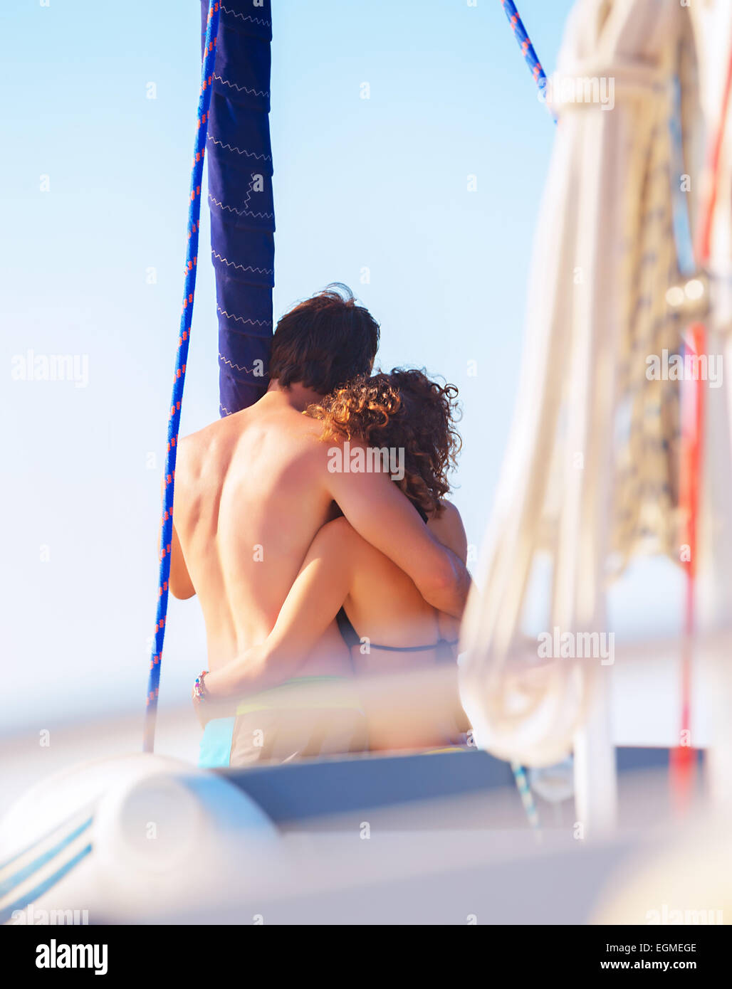 Back side of happy loving couple standing on the mast of luxury sail boat and hugging, enjoying sea view and summer - Stock Image