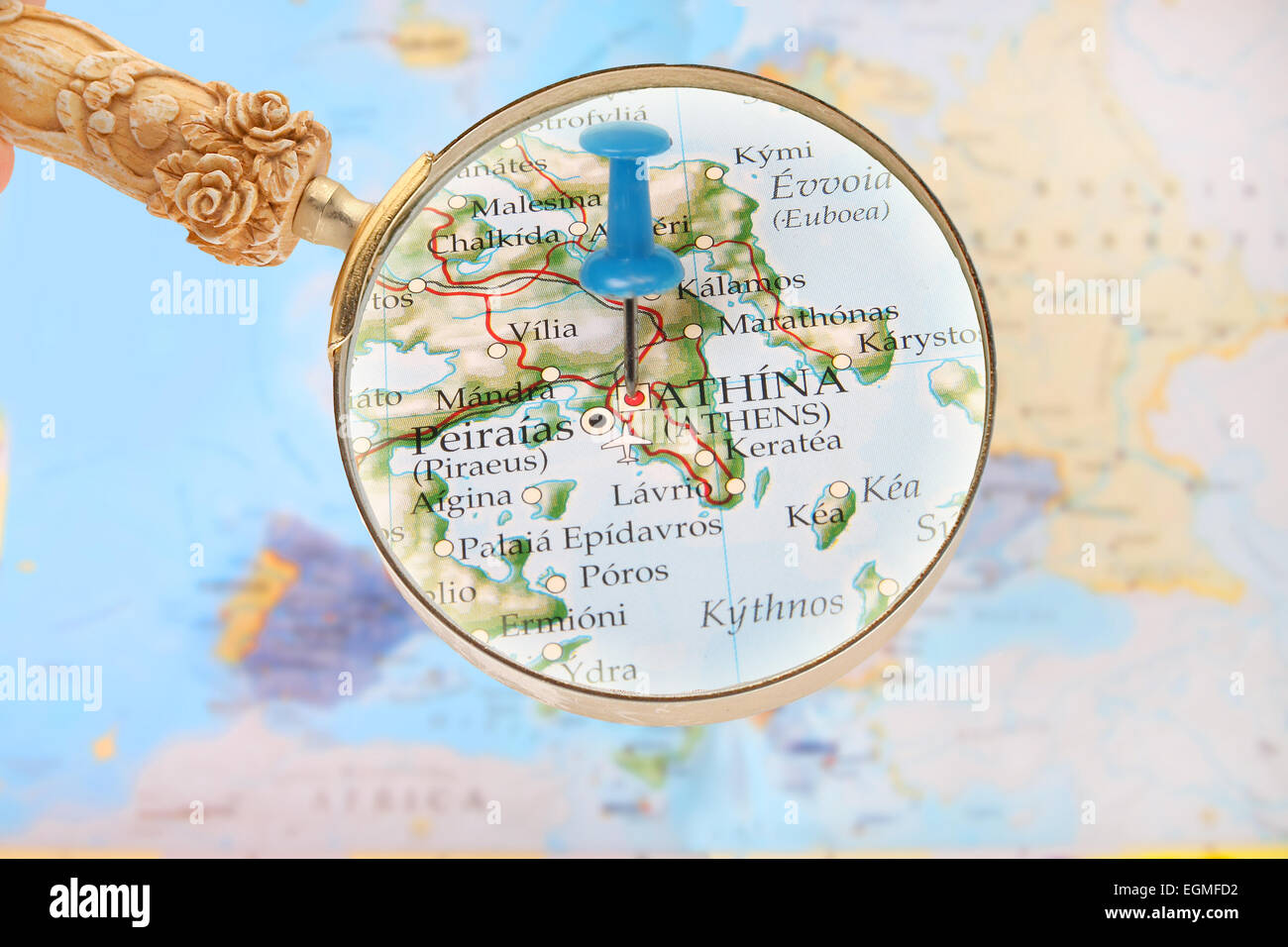 Blue tack on map of Europe with magnifying glass looking in on Athens, Greece - Stock Image